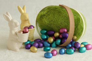 Easter Service Egg Hunts: small basket with chocolate eggs falling out and two porceling bunnies