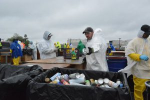 Hazardous Household Materials: people in white hazmat suits sorting materials