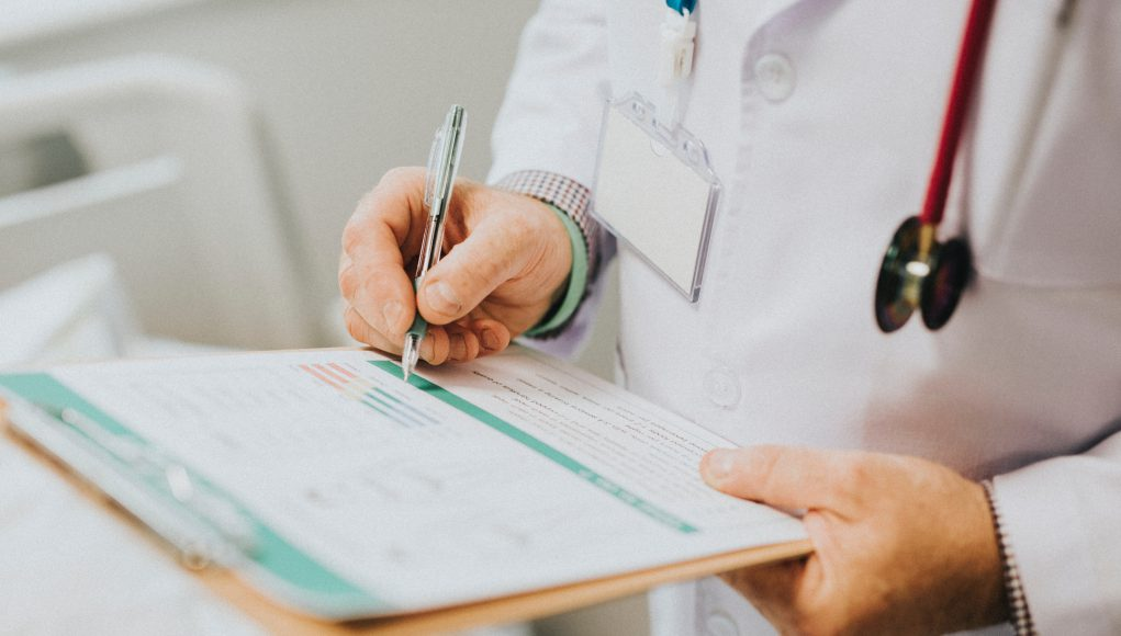 doctor medical center CHI Saint Joseph: doctor with a white lab coat and stethoscope writing on a clipboard