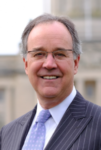 Business News Kentucky Chamber: man in a suit and glasses smiling at the camera