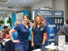 Health: two women dressed in scrubs smiling at the camera