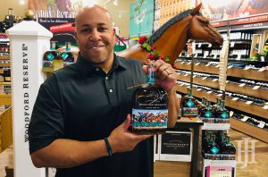 Total Wine: a man in a black polo holding a bottle of bourbon with a fake horse behind him