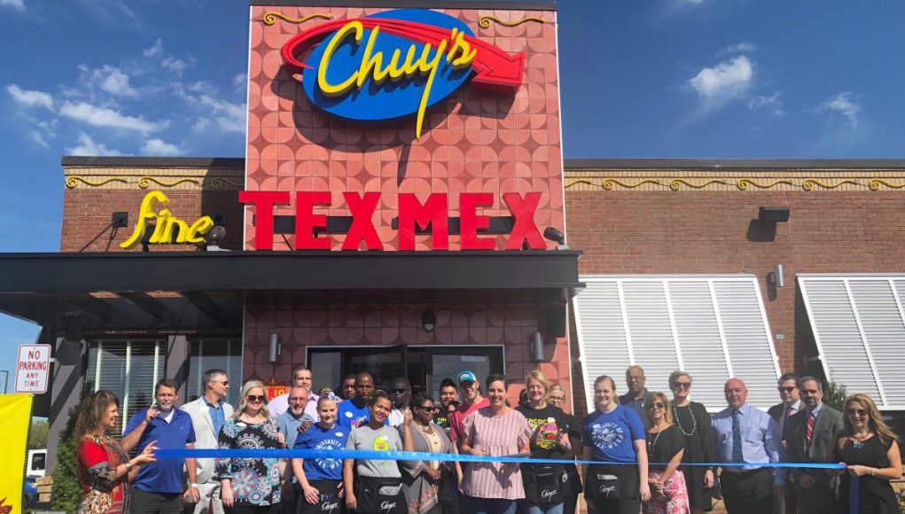 Business: a building that says Chuy's Tex-Mex with a group of people standing in front of it