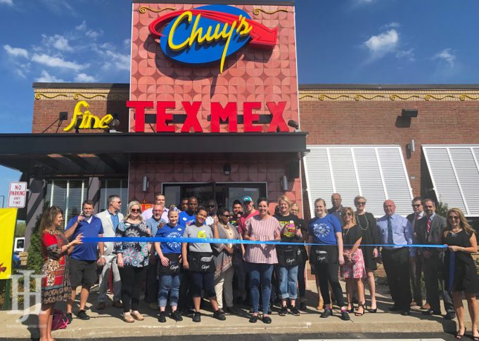a building that says Chuy's Tex-Mex with a group of people standing in front of it
