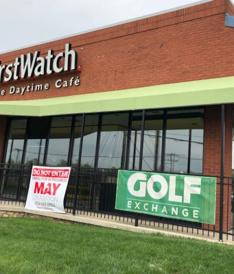 A building with a small black gate in front that says First Watch and a green sign that says Golf exchange