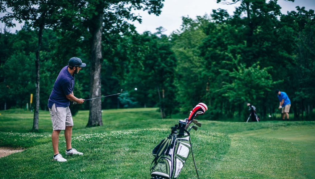 Business Andover Golf Course: a man in a navy polo and hat swinging a golf club