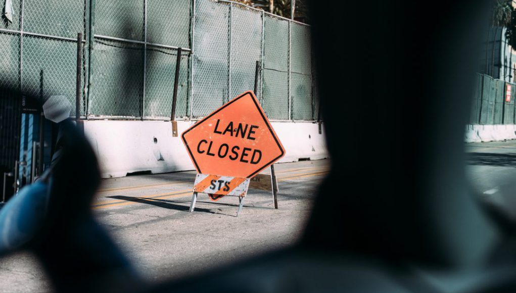 Work Zone: sign of an orange lane closed sign