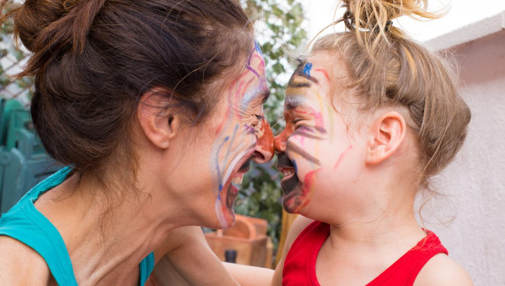 Lexington woman and three years old girl with painted faces, smiling and looking closely, in terrace of house