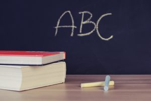 FCPS: chalkboard that says ABC and chalk and books on a table