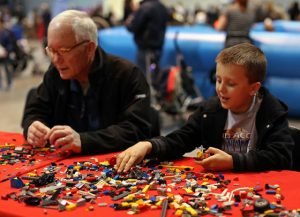 LEGO Convention: an older man and a young boy at a table playing with LEGOs