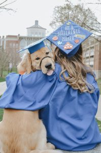 a golden retriever in a graduation cap and a woman in a cap and gown