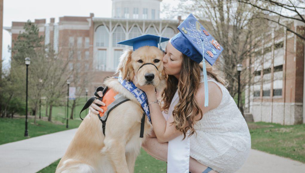 a golden retriever in a graduation cap and a woman in a graduation cap