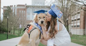 a golden retriever in a graduation cap and a woman in a graduation cap