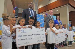 Fayette County Public Schools: group of adults and kids holding up big checks