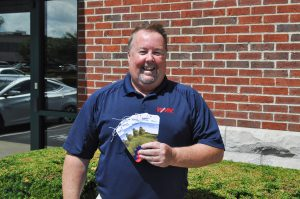 Neighborhood: man holding tickets wearing a navy polo