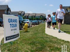 Home and Garden: a sign that says gran tour of homes and people walking by