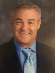 Principal: headshot of a man in a suit