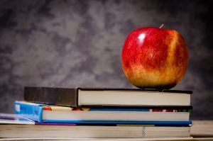 merit scholarship school Parents: blackboard with books on a desk and an apple