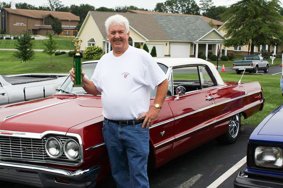 Senior: man with a trophy in front of a classic car