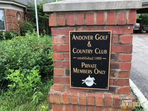 Neighborhood: plaque for a golf course on a brick wall