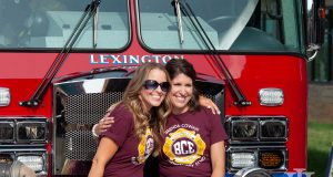Lexington Family: two women in maroon shirts sitting in front of a fire truck smiling at a camera