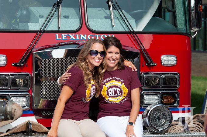 Family: two women in maroon shirts sitting in front of a fire truck smiling at a camera