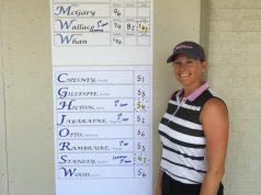 Neighborhood: female golfer posing by the score board