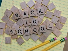 KIds: back to school with scrabble letters on yellow paper and two pencils