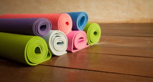 Colorful yoga mats rolled up on a wooden floor in a yoga studio.