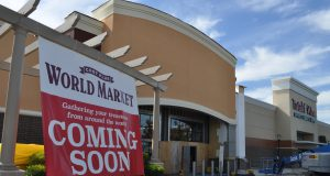 Cost Plus World Market Business: a coming soon sign with a building behind