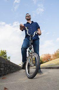 Lexington: a man on a bike with a blue sky behind him
