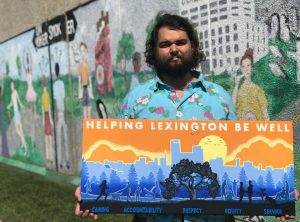 Health: a man holding a painting with a mural behind him