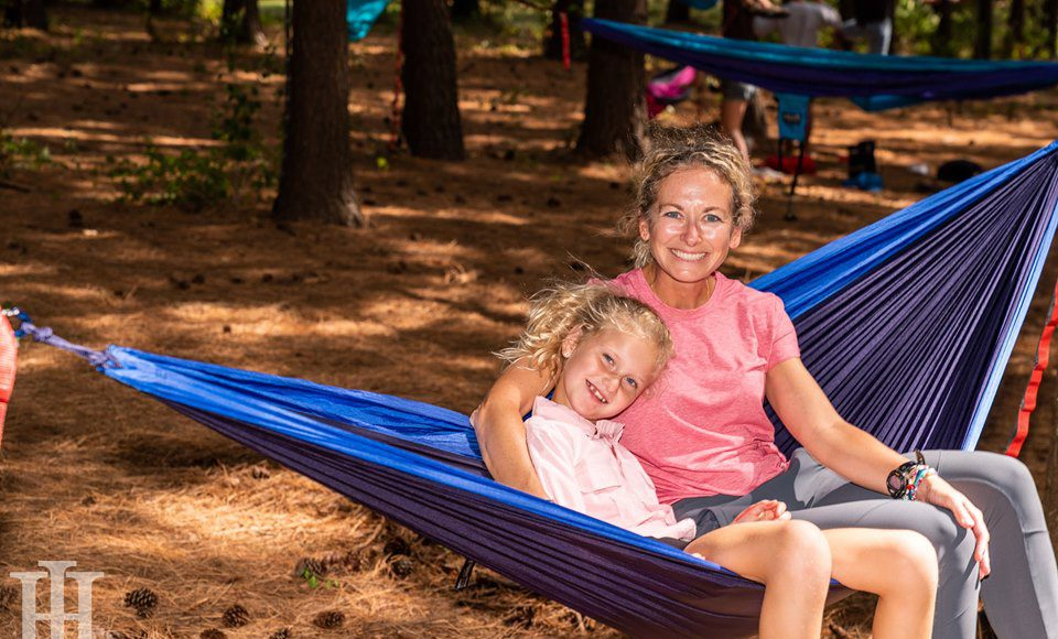 Neighborhood: a mother and daughter sitting in a hammock surrounded by trees