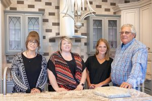 Hager Cabinets: four people around a kitchen island smiling at the camera