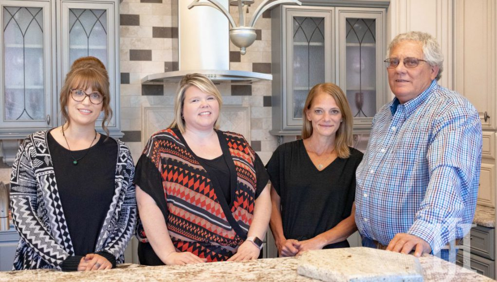 home and garden Hager Cabinets: four people around a kitchen island smiling at the camera