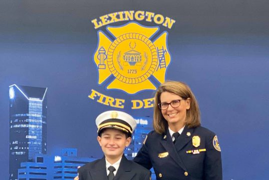 Family: a young boy and older woman dressed in fire chief uniforms