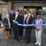 Business: group of people cutting a ribbon in front of a hotel