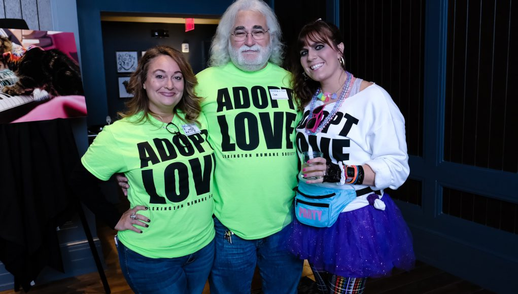Pet: group of people wearing lime green shirt that says adopt love and a girl dressed from the 80's
