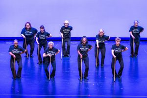 Senior Living: group of older women dancinc with canes and in black outfits