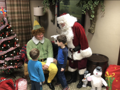 family holiday guide Neighborhood: a man dressed as elf and santa claus with kids