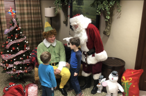 holiday guide Neighborhood: a man dressed as elf and santa claus with kids