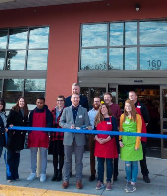 World Market: group of people standing outside of a building with ribbon