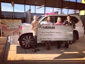 neighborhood: group of girls holding a giant check with a car behind them