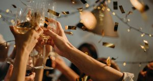 New Year's Eve: people clanking glasses with confetti